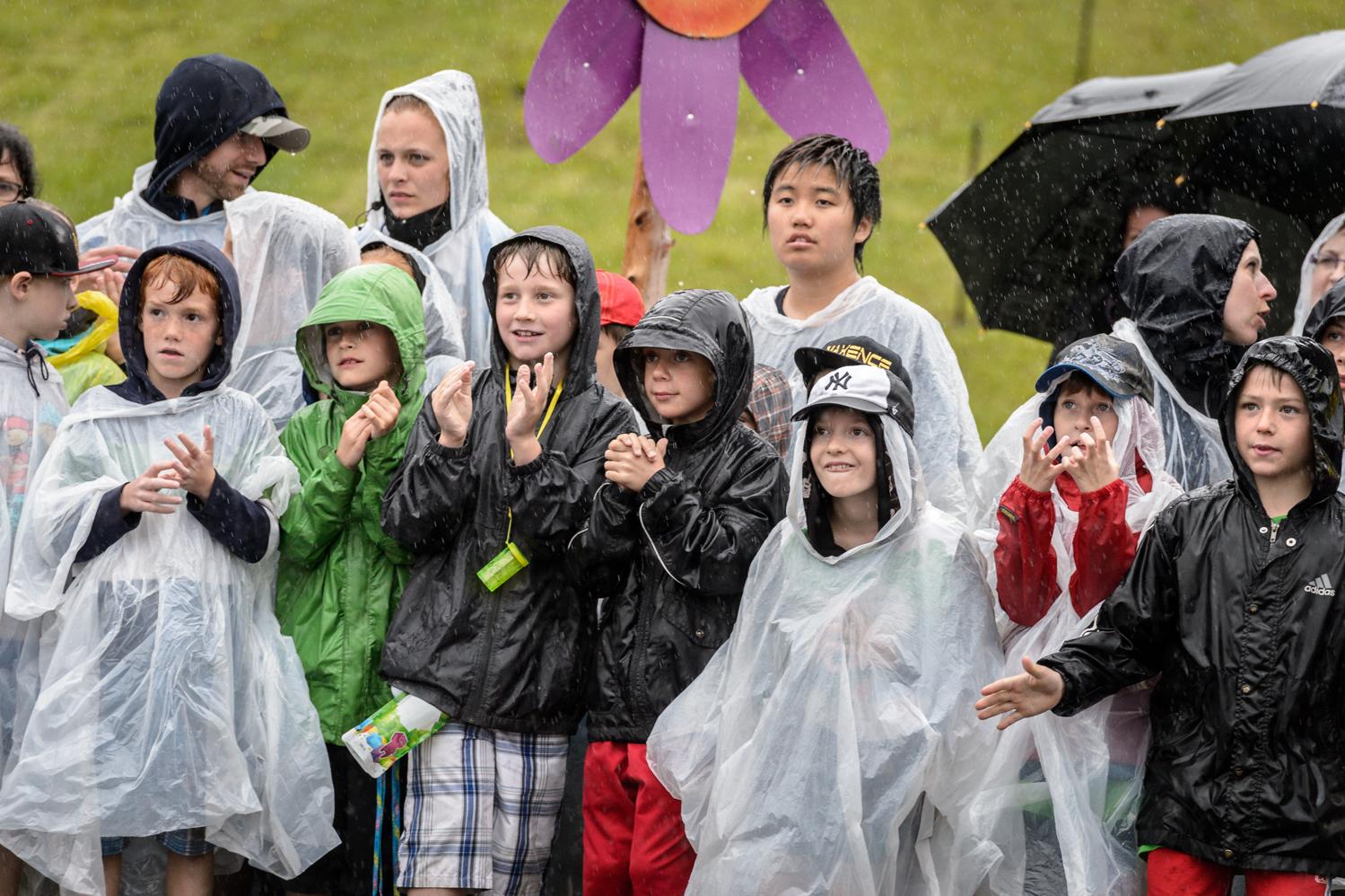 Les spectateurs attendent l'arrivée des premiers cycliste sous une pluie battante.