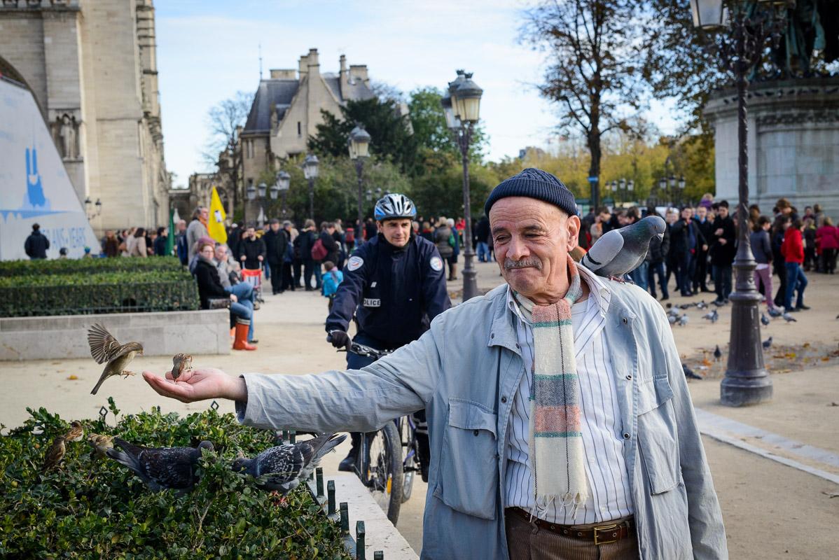 Un homme du coin qui attire les pigeons et les oiseau pour les nourrir. Juste avant que le policier ne l'avertisse...